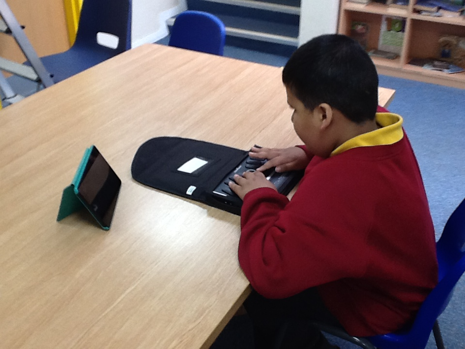 One of our Braille students using an electronic braille note to record his ideas. The Kindle is used for the teachers and staff to read in print what Haaris is brailling